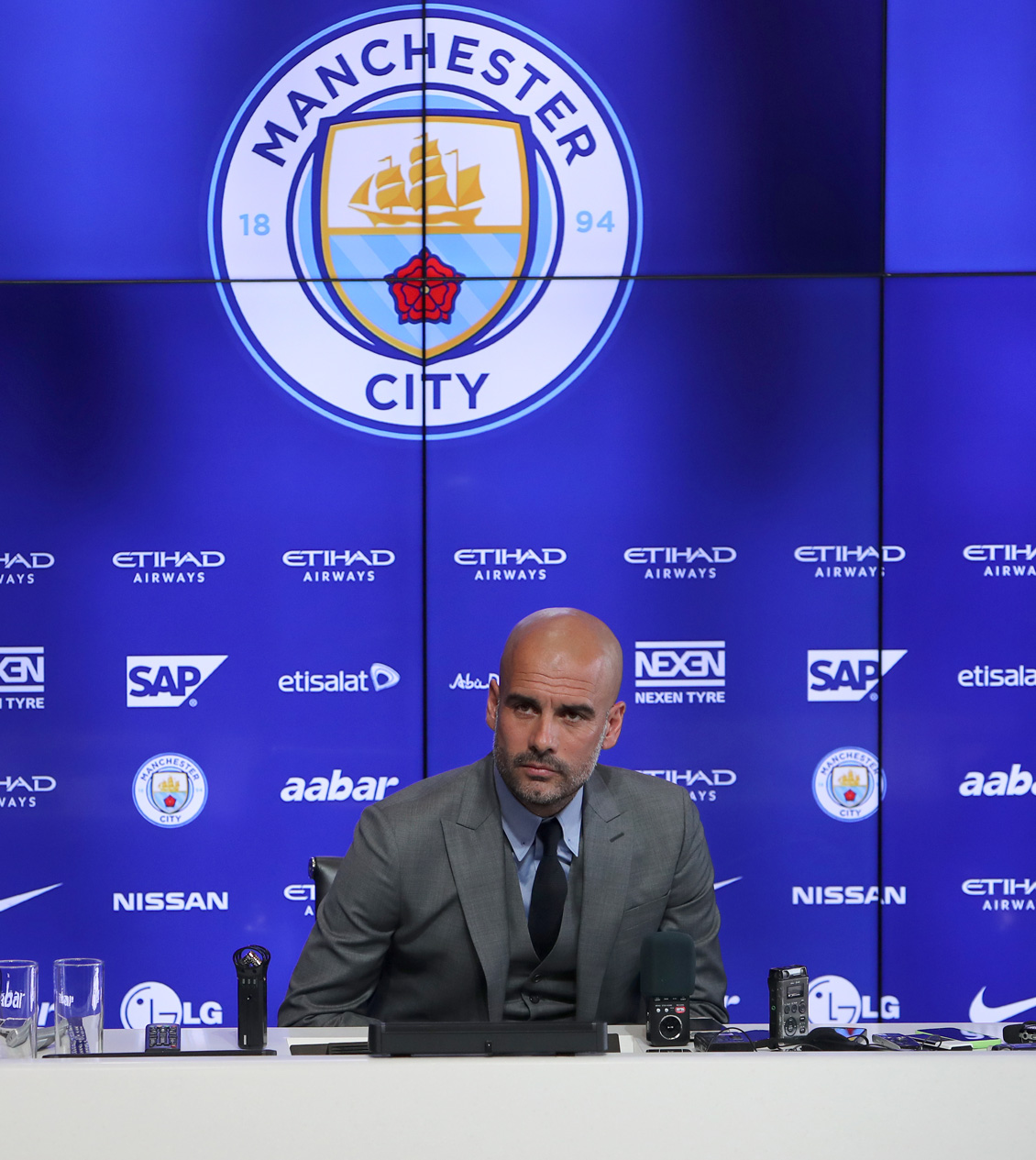 Pep Guardiola at a Manchester City press conference supported by Etihad Etisalat SAP AAbar Nexen Nissan and LG